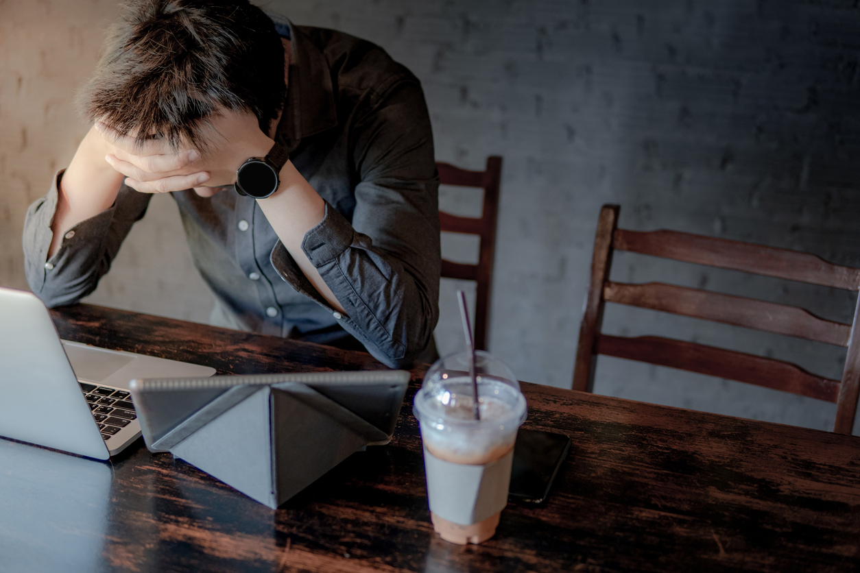 Overworked Asian businessman or male entrepreneur feeling stressed and frustrated while working with laptop computer and digital tablet in the cafe. Tired and headache from work hard or failure.